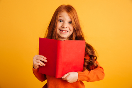 Image of cheerful little redhead girl with freckles standing isolated over yellow background reading book. Looking camera.