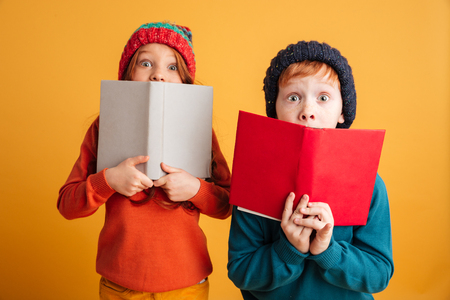 Image of two scared little redhead children with freckles standing isolated over yellow background wearing warm hats. Looking camera covering faces with books.