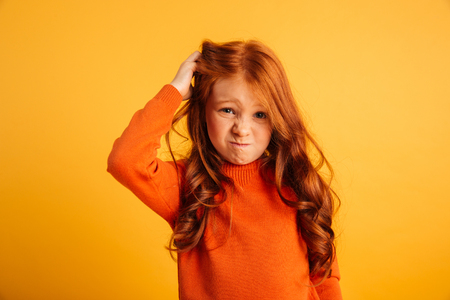 Photo of confused little redhead girl with freckles standing isolated over yellow background. Looking camera.