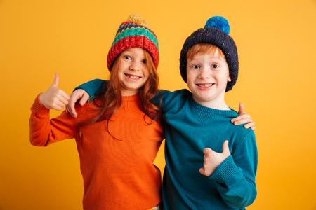 Bild von zwei lustigen kleinen Kindern , die über gelbem Hintergrund stehen , um warme Hüte trägt . Kamera zeigen Daumen hoch .