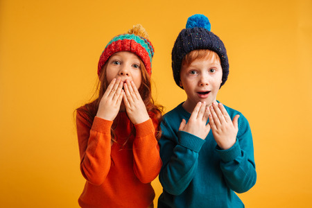 Photo of two shocked surprised little children isolated over yellow background wearing warm hats. Looking camera with mouth opened.