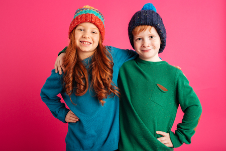 Photo of two happy little children isolated over pink background wearing warm hats. Looking camera. Banco de Imagens