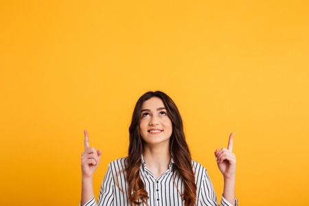 Picture of Smiling brunette woman in shirt pointing and looking up over yellow background