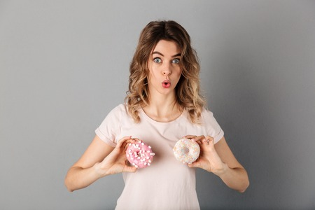 Funny woman in t-shirt showing donuts and looking at the camera over grey background