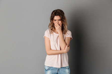 Upset woman in t-shirt crying and covering her mouth while looking down over grey background