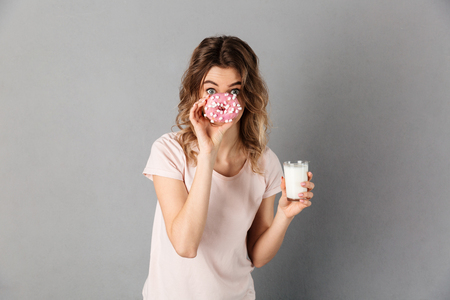 Playful woman in t-shirt hiding behind donut while holding milk and looking at the camera over grey background