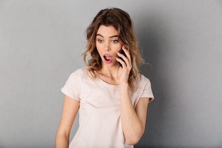 Shocked woman in t-shirt talking by smartphone and looking down over grey background