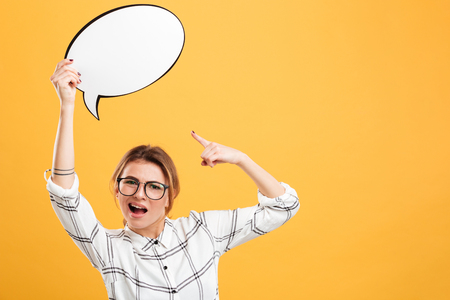 Photo of caucasian woman 20s wearing eyeglasses holding blank speech bubble and pointing finger on it isolated over yellow background