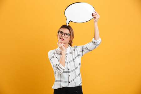 Portrait of brooding woman 20s wearing eyeglasses holding blank speech bubble and looking aside isolated over yellow background
