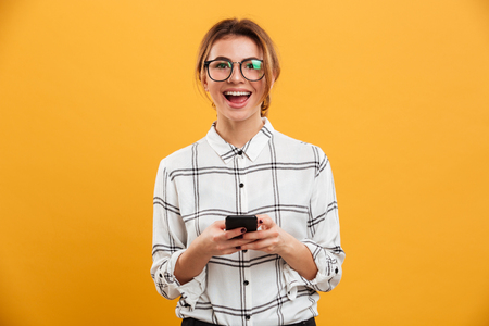 Portrait of beautiful woman in plaid shirt and eyeglasses posing on camera with mobile phone in hands isolated over yellow background Foto de archivo