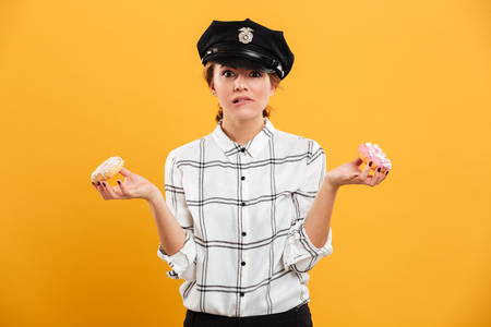 Portrait of smiling woman in plaid shirt and police cap posing on camera with donuts in hands isolated over yellow background Stock Photo