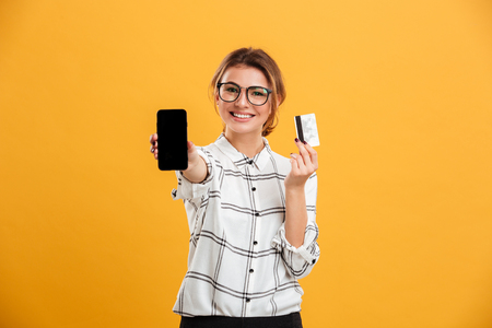 Portrait of cheerful woman wearing eyeglasses holding smartphone and credit card in hands isolated over yellow background
