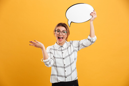 Photo of surprised woman 20s wearing eyeglasses holding blank speech bubble and throwing hand aside isolated over yellow background