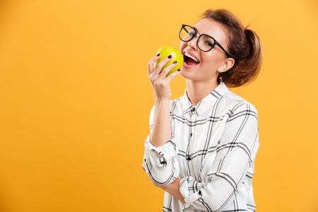 Portrait closeup of smiling woman in plaid shirt and eyeglasses eating green apple with pleasure isolated over yellow background