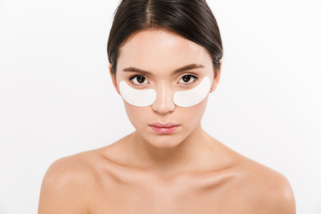 Beauty portrait of brunette asian woman wearing cosmetic patches under both eyes and looking on camera isolated over white background