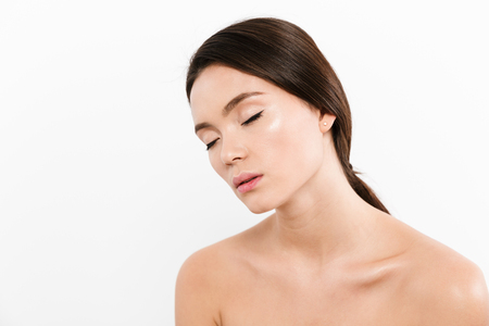Beauty portrait of shirtless asian woman having brown hair in ponytail relaxing with closed eyes in half-turn isolated over white background