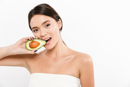 Beauty portrait of brunette asian woman biting and eating half of fresh ripe avocado isolated over white background