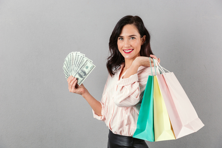 Portrait of a cheery businesswoman holding bunch of money banknotes while carrying shopping bags isolated over gray background
