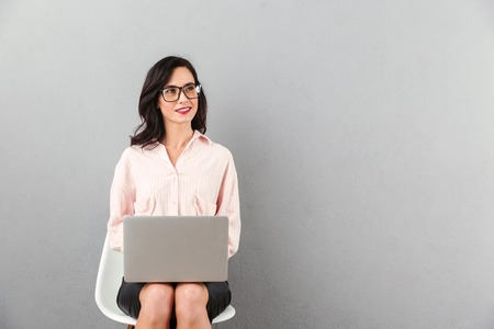 Portrait of a smiling businesswoman in eyeglasses looking away at copy space while sitting in a chair and using laptop computer isolated over gray background