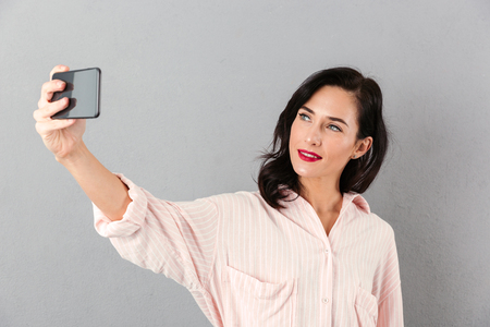 Portrait of a beautiful businesswoman taking a selfie isolated over gray background