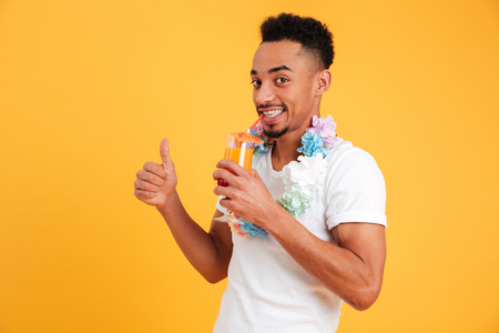 Portrait of a happy african man dressed in summer outfit drinking cocktail and showing thumbs up isolated over yellow background