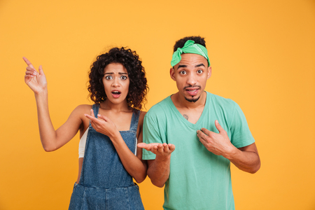 Portrait of a confused young african couple dressed in summer clothes pointing fingers isolated over yellow background