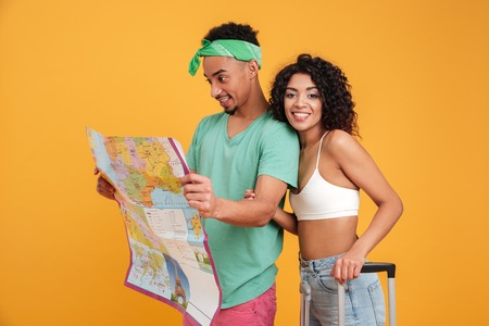 Portrait of a cheerful young african couple in summer clothes looking at city guide map isolated over yellow background