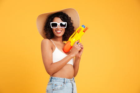 Portrait of a cheerful young african woman dressed in summer clothes holding water pistol and looking at camera isolated over yellow background