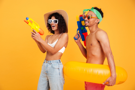 Portrait of a happy young african couple in summer clothes holding water pistols and infltable ring isolated over yellow background