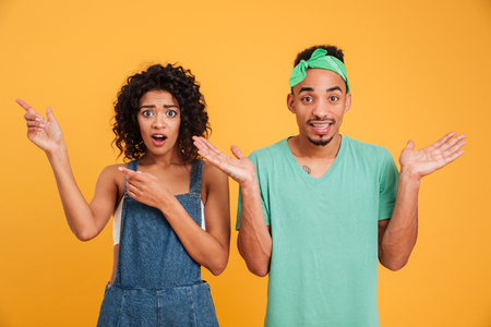Portrait of a puzzled young african couple dressed in summer clothes pointing fingers isolated over yellow background