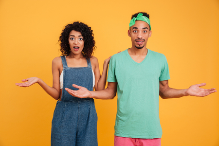 Portrait of a confused young african couple dressed in summer clothes shrugging shoulders isolated over yellow background