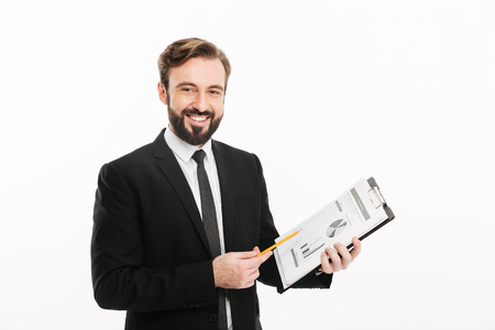 Photo of cheerful businessman standing isolated over white background looking camera holding documents.