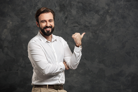 Portrait of a happy young man dressed white shirt pointing finger away over gray background