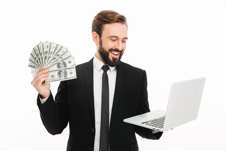 Portrait of mature male entrepreneur holding laptop and lots of money dollar currency isolated over white background