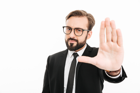 Image of serious businessman standing isolated over white background showing stop gesture.