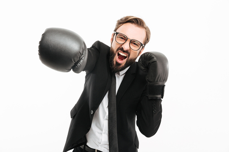 Portrait of aggressive businessman in black suit and eyeglasses screaming while punching on camera in boxing gloves isolated over white background