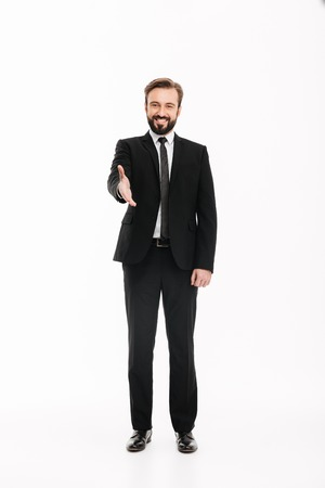 Image of handsome young businessman standing isolated over white background give you a hand for handshake. Looking camera.