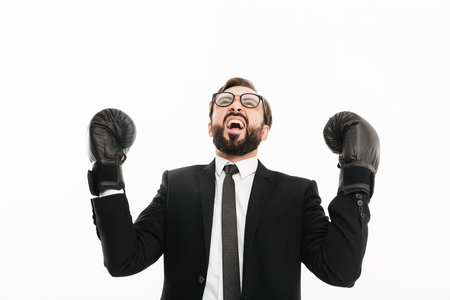 Portrait of emotional businessman in black suit and eyeglasses rejoicing his win in boxing gloves, isolated over white background Stock Photo