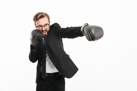 Portrait of decisive business man in black suit and eyeglasses emoionally punching aside in boxing gloves isolated over white background Stock Photo