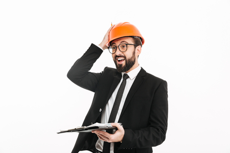 Image of happy engineer businessman in helmet standing isolated over white background looking aside holding documents. Stok Fotoğraf