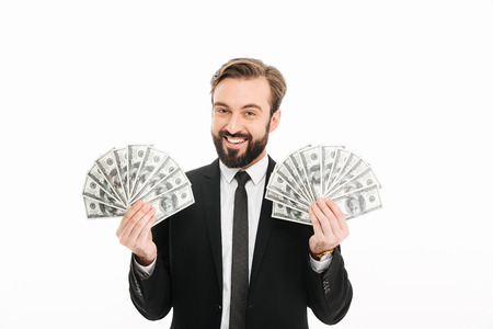Portrait of delighted rich male millionaire holding two fans of money 100 dollar banknotes isolated over white background