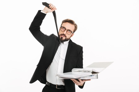 Photo of tired young businessman standing isolated over white background. Looking aside displeased because of work documents in folders.