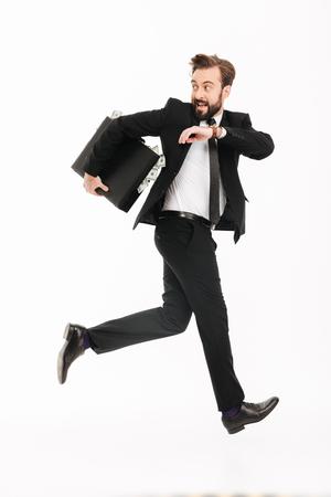 Beeld van opgewekte jonge zakenman met koffer lopen geïsoleerd over witte achtergrond. Opzij kijken.