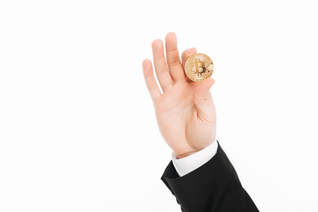 Close up cropped image of male hand in suit holding golden bitcoin or digital money on camera isolated over white background Фото со стока