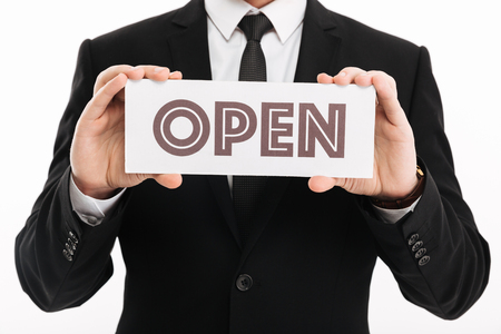 Image cropped of businesslike man in suit and tie holding open sign on camera isolated over white background Stockfoto
