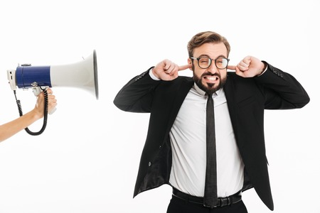 Image of confused businessman standing isolated over white background covering ears because of loudspeaker. Stock Photo