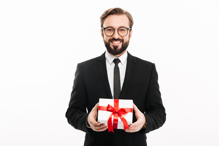 Portrait of smiling brunette man in black suit looking on camera and holding small gift box in hands isolated over white background