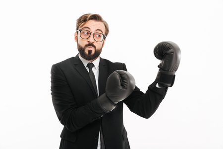 Portrait of courageous business man in suit and eyeglasses boxing in black gloves isolated over white background