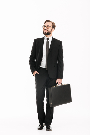 Full-length image of wealthy businesslike man in suit and eyeglasses carrying black briefcase and looking aside isolated over white background