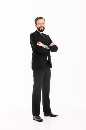Photo of cheerful young businessman standing isolated over white background. Looking camera with arms crossed.